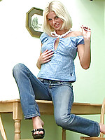 Nastika strips as she gets ready to touch herself on her kitchen table