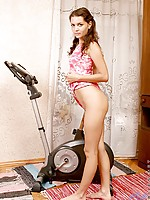 Curly haired hottie teasing and posing on her fitness bike