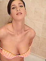 See this cutie in the shower getting wet and touching her round boobs